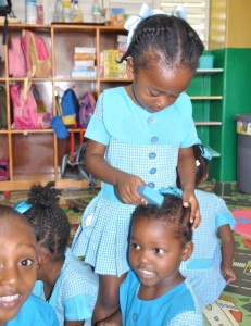 Hairdresser for the day, Zehida Alleyne, fixing Jamira Fields with a fine hairstyle, as another student looks on curiously.