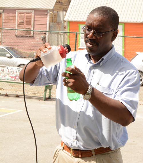 Errol Goodridge of the Labour Department advising children against pouring chemicals into unmarked containers.