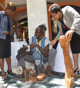 """Director of Research and Planning in the Ministry of Tourism, Francia Jordan (left), and CEO of the SBA, Lynette Holder looking at the creations of Chesterfield """"Rass Ilix"""" Perch of Temple Yard."""