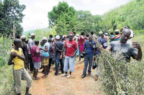 Residents gather at the murder scene, yesterday.