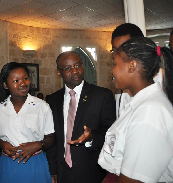 Minister of Culture, Sports and Youth Stephen Lashley (left) interacting with                    students who attended the launch  of the Youth Parliament.