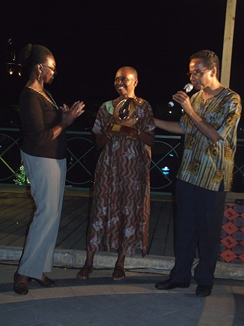 Wife of David Comissiong, Sally (centre) presented the Clement Payne Cultural Achievement Award 2014 to the wife of Kamau Braithwaite, Beverley. At right with microphone is David Comissiong.