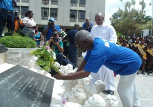 Sir Roy Trotman lays a wreath at the feet of the statue of Sir Frank Walcott. In background is Dean Frank Marshall