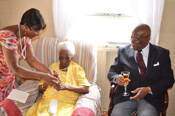 Governor General Sir Elliott Belgrave (right) prepares to have a toast with  centenarian Iona Viola Griffith (centre) who is being assisted by her daughter Eleanor Griffith.