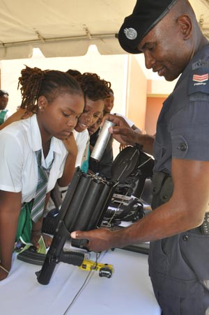 Sergeant Derrick Babb (right) of the Royal Barbados Police Force demonstrating to students how to load a rifle.