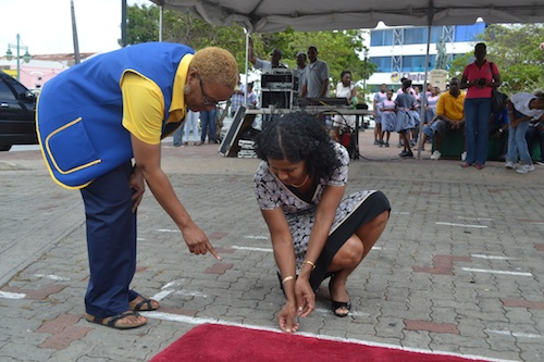 Minister of Labour Dr Esther Byer-Suckoo lays silver dollars coins under the guidance of Jennifer Hinkson, chairman of Kiwanis Silver Dollars project.