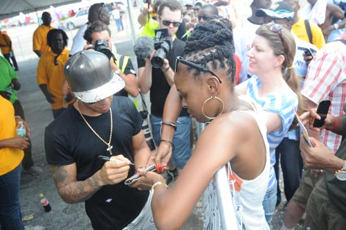 Formula One driver Lewis Hamilton, who is top of the F1 table after four race wins this season, signing autographs for fans