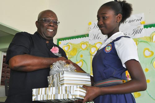 Headgirl Tyeisha Cummins presenting a prize to retiring teacher Charles Ifill.
