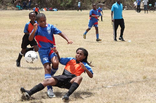 Wilkie Cumberbatch's goal scorer Isheim Brewster goes down to clear the ball from Jaden Walcott of People's Cathedral.