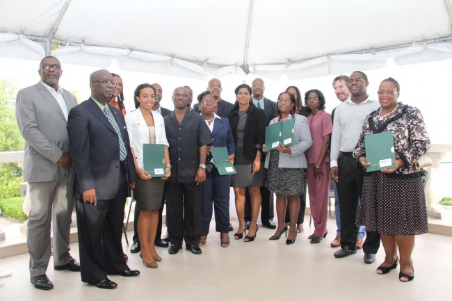 Minister of Education Ronald Jones (at left) and Minister of Labour Dr Esther Byer-Suckoo (centre), posing with IDB officials and representatives of local training institutions and businesses.