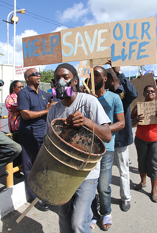 Akemo Cobom leading Silk Cotton Road, Marabella residents during a protest outside Petrotrin's headquarters in Pointe-a-Pierre yesterday.