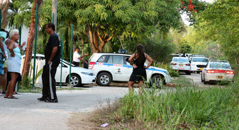 Police and local residents converge on the scene of Tuesday afternoon's machete attack in Bodden Town.