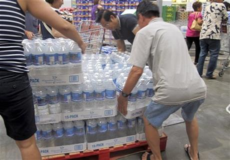 Shoppers lift cases of bottled water in preparation for a hurricane and tropical storm heading toward Hawaii at the Iwilei Costco in Honolulu yesterday.