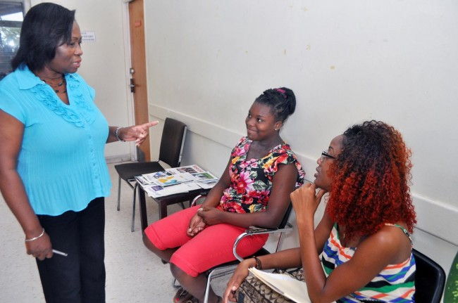 New Graydon Sealy Secondary principal Beverly Bancroft in conversation with two students of Springer Memorial while at the school in Government Hill      during the summer holidays.