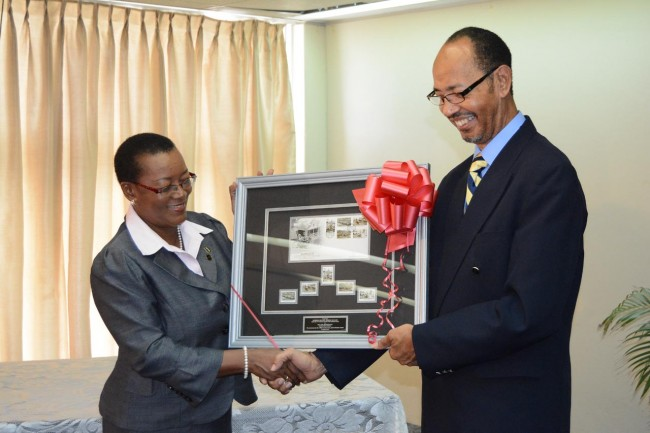 Minister of Foreign Affairs and Foreign Trade Senator Maxine McClean receives a set of the commemorative stamps issued by the Philatelic Bureau to mark the 100th Anniversary of The Panama Canal from                                          Postmaster General Joel Brathwaite.