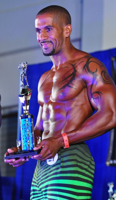Marlon Dottin posing with his men's physique trophy.