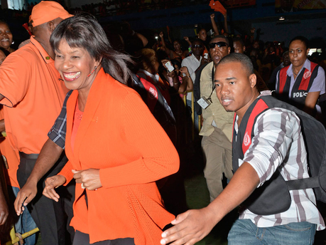 Prime Minister Portia Simpson Miller, president  of the People's National Party, sprinting to the stage, as security personnel provided cover during the party's 76th annual conference at the National Arena in St Andrew yesterday.