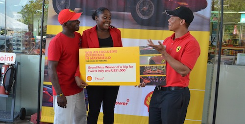 Marketing manager of Sol Barbados, Kirk KIng (right) has the attention of winner Kerri Stuart (centre) and her father Dalson Selman, during the presentation ceremony at Shell Top Rock, Christ Church yesterday.