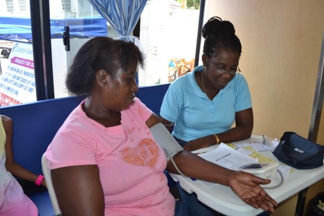 Marva Smith having her blood sugar checked by Lorraine Scantlebury.
