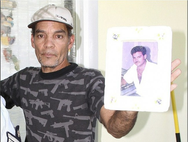 A family member holds up a picture of 44-year-old Andre Cartwright at his Blair Estates home yesterday.