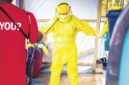 A health care worker in protective gear is sprayed with disinfectant after working in an Ebola treatment centre in the west of Freetown yesterday.