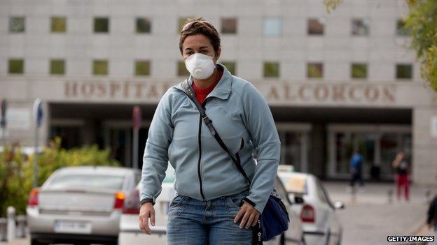 A woman wears protective mask as she leaves Alcorcon hospital.