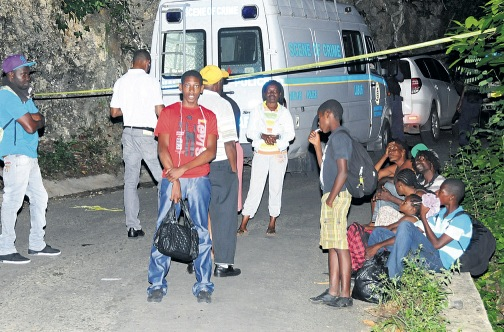 Curious onlookers gather behind the police tape as cops  process the crime scene where four workers of the Mount Rosser leg of Highway 2000 were brutally murdered by gunmen.