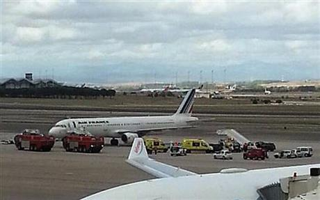 Emergency crews stand next to a plane, carrying 163 people, at the Madrid Airport, Spain, today.
