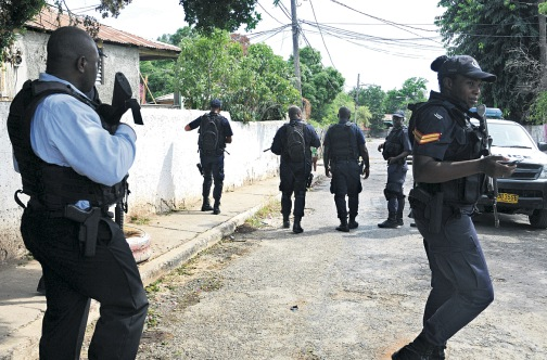 Police patrol a street in Rockfort, east Kingston yesterday, a day after three men were shot dead by gunmen in the community.