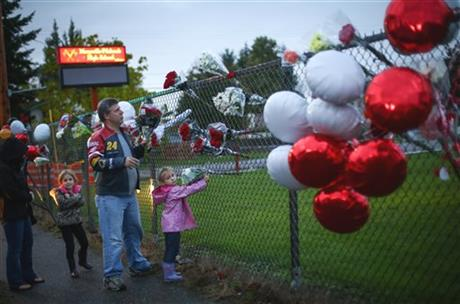 Rick Hartwig places flowers with his daughters Cailin, 6, and Chloe, 5, right, as the memorial grows Saturday Oct. 25, 2014 at the entrance to Marysville Pilchuck High School.