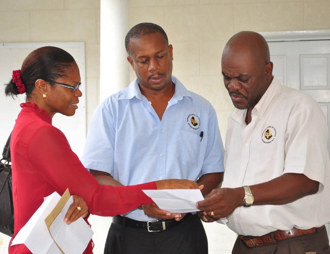 A TEACHER'S COMPLAINT She's one of the senior teachers at Parkinson Memorial who were off the job today complaining about their principal's management style.  Here, Janice Hutchinson  (backing the camera) makes a point to Barbados Union of Teachers President Pedro Shepherd and Vice President Richmark Cave.