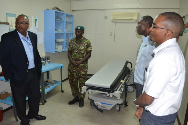 Officer in charge of the BDF medical centre, Lt. Sean Broome discusses the services offered during a tour by Minister John Boyce (second from left). Other military and health officials look on.