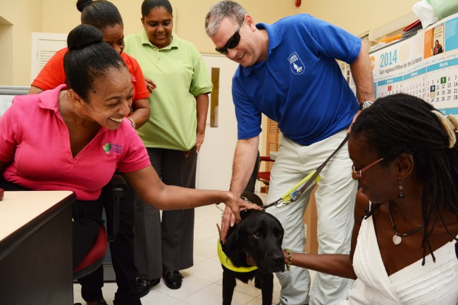 Dylan being petted by employees at the Barbados Council for the Disabled as his  owner Danny Gleeson holds on to his leash.