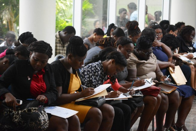 Hopeful jobseekers filling out applications for a job with Sandals Barbados.