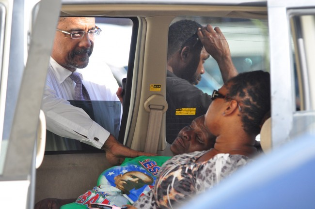 High Court judge and friend of the deceased, Randall Worrell, comforts Craig's life-long companion Mabel Small at the scene of the tragedy.