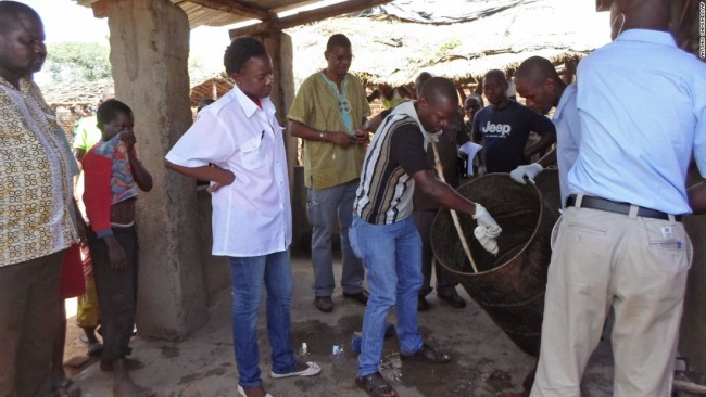 Mozambique government officials gather samples from a drum that was allegedly used to make local beer.