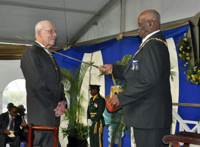 Barbados' newest Knight, Sir Henry Fraser, has the award conferred on him by Governor General, Sir Elliott Belgrave.