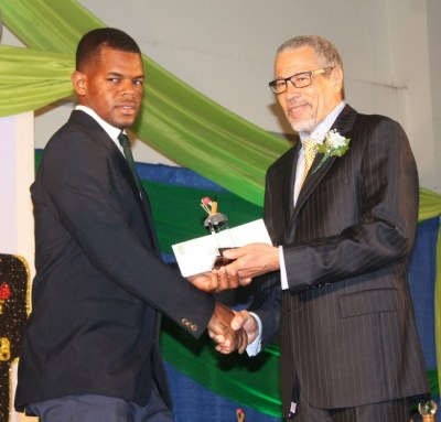 Antonio Greenidge of BDF Sports Programme accepting his most improved cricketer of the year trophy from David Deane.