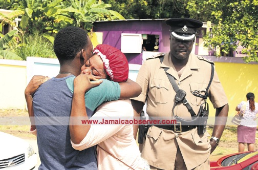 Jacinth Johnson, mother of 12-year-old Shyheim Lewis who was fatally stabbed by his classmate, is comforted yesterday by her spouse Linton White outside the Barrett Town All Age School as Police Superintendent Gary Francis looks on.