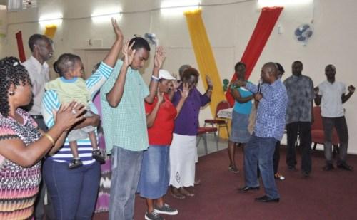 Prophet Abraham Obanrewaju praying  for congregation members at Victorious Living Ministries.