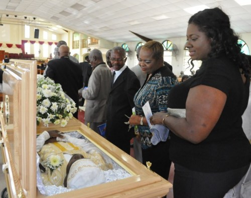 Viewing a departed comrade are (from right) calypsonian Christine Eli and All Stars Calypso Tent manager Eleanor Rice.