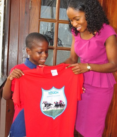 Xavier Bertrand receiving  his Sandy Lane Gold Cup race  T-shirt from BT Sales  Representative Omisa Hobbs.