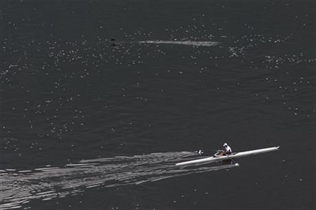 A man rowing in the Rodrigo de Freitas lagoon, surrounded by dead small silvery fish, in Rio de Janeiro, Brazil.