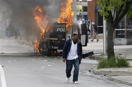 A man walks past a burning police vehicle, Monday, April 27, 2015, during unrest following the funeral of Freddie Gray in Baltimore. Gray died from spinal injuries about a week after he was arrested and transported in a Baltimore Police Department van.