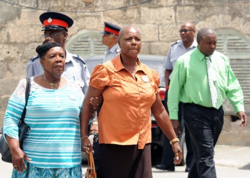 A distressed Marlene Knight being escorted across the courtyard by a close friend.