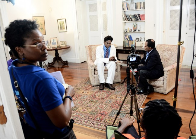"""Director and acting Web content manager Esther Jones ensuring """"quiet on the set"""" during a """"take"""" of veteran journalist Tony Cave's interview with  National Hero Clement Payne, portrayed by actor Angelo Lascelles."""