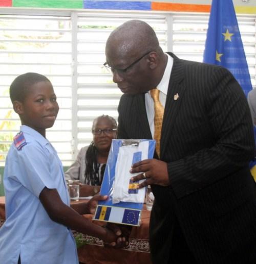 Minister of Education Ronald Jones presenting Tafari Coward with his kit.