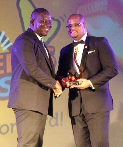NISE director Alex McDonald (right) presenting the Customer Service Award For Medium-Sized Business to a representative of Dial (Barbados) Inc.