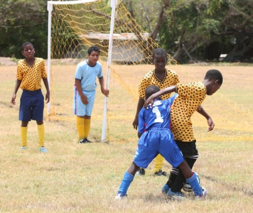 Matthieu Clarke (number one) and St Ambrose goal-scorer Tafari Coward battle for ball possession while other players look on.