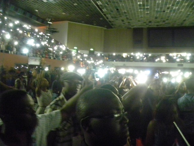 THE GYMNASIUM LIGHTS WENT DOWN AND A MASS OF CELLPHONE LIGHTS CAME ON